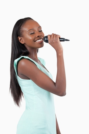 Smiling young female singer against a white background photo