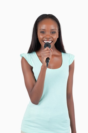Brightly smiling young female singer against a white background Stock Photo - 11636434