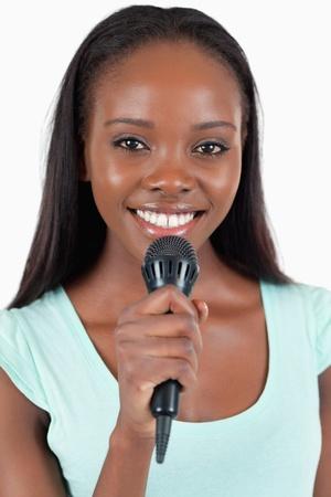 kareoke: Close up of happy smiling female singer against a white background Stock Photo