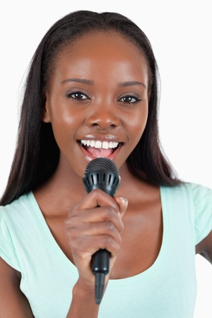 kareoke: Close up of brightly smiling female singer against a white background