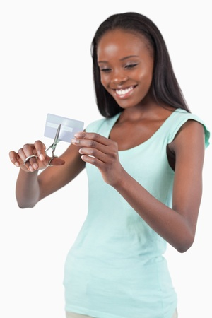 Smiling woman cutting her credit card into pieces against a white background photo
