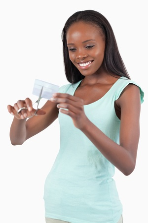 Smiling young woman destroying her credit card against a white background Stock Photo - 11634941