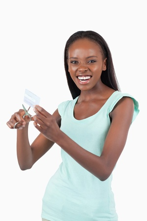 Angry woman destroying her credit card against a white background photo