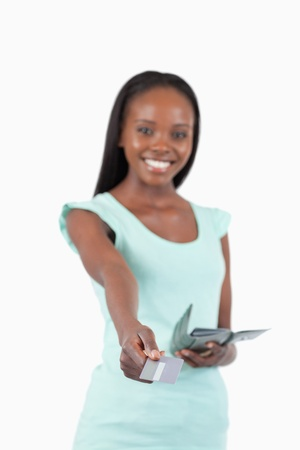 Smiling young woman paying with her credit card against a white background Stock Photo - 11624760