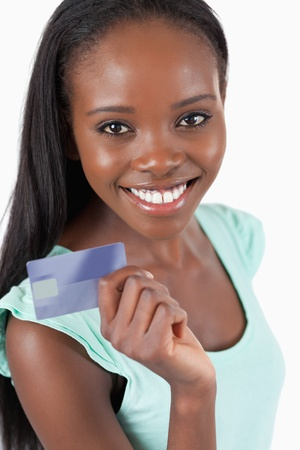 Smiling young woman with her new credit card against a white background photo