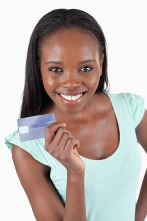 transaction: Smiling young woman showing her credit card against a white background