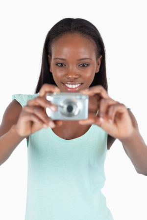 digi: Smiling young woman using her digi cam against a white background