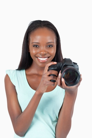 Smiling young photographer with her camera against a white background photo