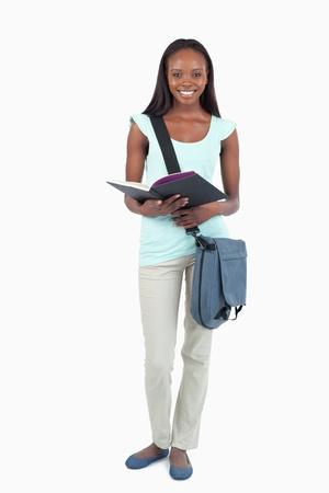 african student: Sorridente giovane studente con il suo libro contro uno sfondo bianco