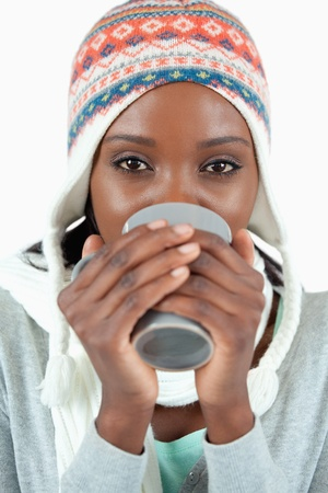 Young woman enjoying tea in the cold against a white background photo