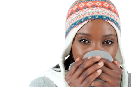 Student woman enjoying a cup of tea in the cold against a white background photo