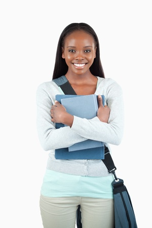 Smiling young female student with books and bag against a white background photo