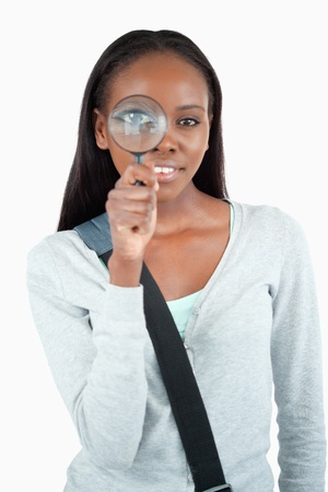 detecting: Smiling young woman with magnifier against a white background Stock Photo