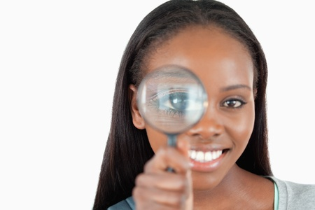 detecting: Smiling woman with magnifier against a white background