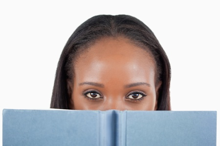 Young woman behind her book against a white background Stock Photo - 11634608
