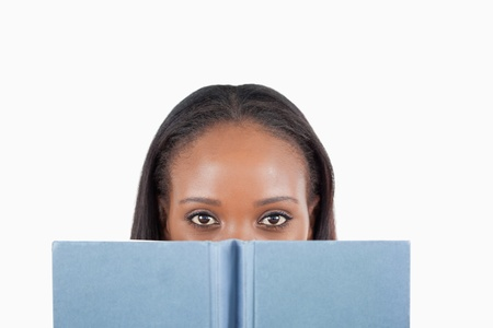 Young woman behind book against a white background photo
