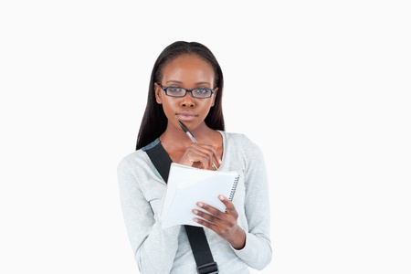 Young woman with glasses and notepad against a white background photo