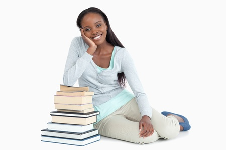 Smiling young woman leaning against a pile of books against a white background Stock Photo - 11624863