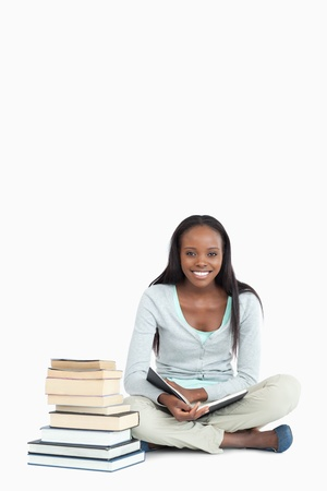 Smiling young woman sitting next to a pile of books against a white background Stock Photo - 11623941