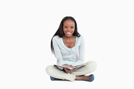 Smiling young woman sitting on the floor with a book against a white background Stock Photo - 11623688