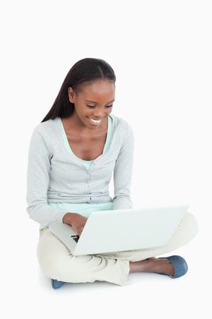 chat online: Smiling woman working on her laptop sitting on the floor against a white background