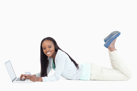 Side view of woman lying on the floor with her notebook against a white background Stock Photo - 11623857