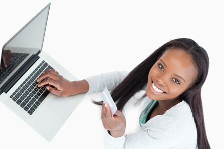 Smiling woman booking flight online against a white background photo