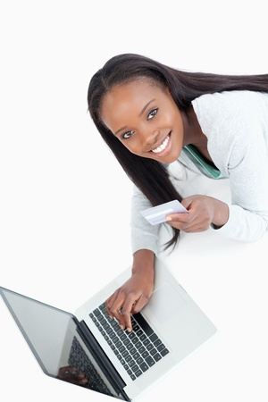 Smiling woman entering credit card information against a white background photo