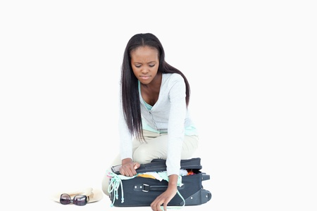 Young woman having problems closing her suitcase against a white background photo