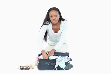 Young woman having problems packing her suitcase against a white background photo