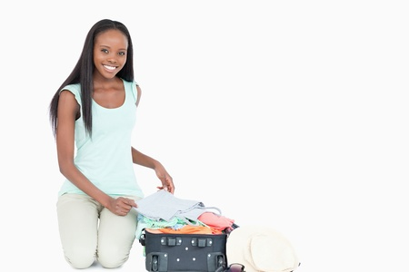 Smiling young woman packing her suitcase against a white background photo