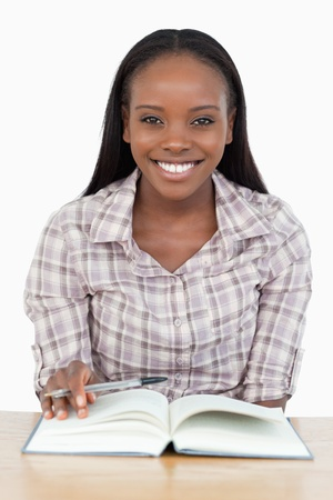 Smiling girl reading a novel against a white background photo