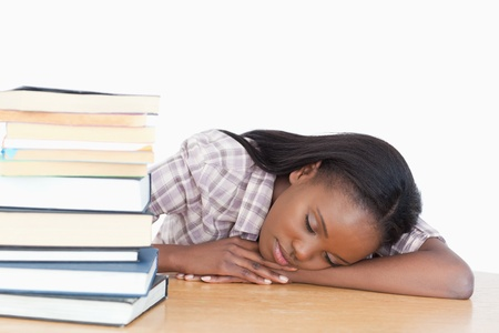 Student sleeping on her desk against a white background photo
