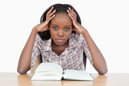 Bored student trying to read a book against a white background photo