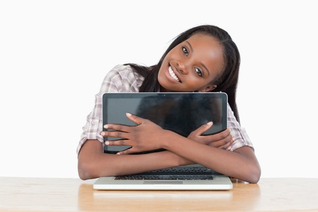 Young woman hugging her laptop against a white background