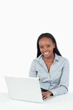 Portrait of a smiling businesswoman using a laptop against a white background photo