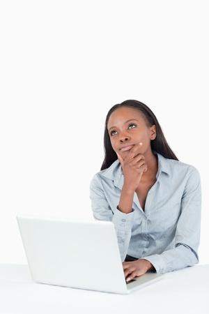 Retrato de una mujer de negocios pensativa con un ordenador port�til sobre un fondo blanco Foto de archivo - 11624781