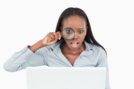Businesswoman using a magnifying glass to look at her laptop against a white background