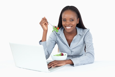 Joyful businesswoman working with a laptop while eating a salad against a white background photo