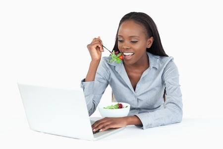 Businesswoman working with a laptop while eating a salad against a white background photo