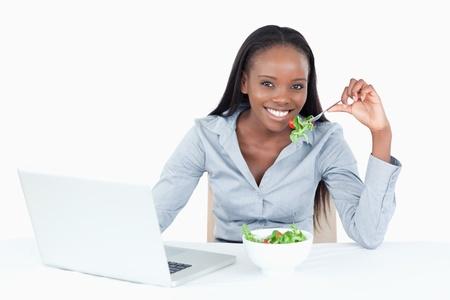 lunchen: Leuke zakenvrouw werken met een notebook, terwijl het eten van een salade tegen een witte achtergrond