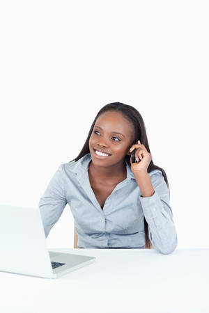 Portrait of a woman making a phone call while using a notebook against a white background photo