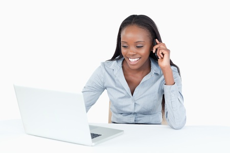Businesswoman making a phone call while using a notebook against white background photo