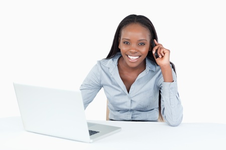 Businesswoman making a phone call while using a laptop against a white background photo