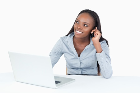 Smiling businesswoman making a phone call while using a laptop against a white background photo
