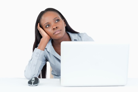 Businesswoman day dreaming while using a laptop against a white background photo