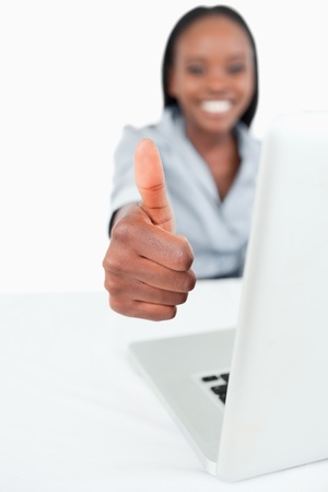Portrait of a businesswoman using a laptop with the thumb up against a white background photo