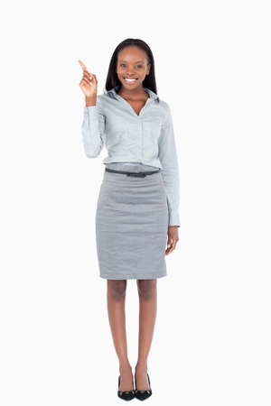 Portrait of a businesswoman pointing at something against a white background photo