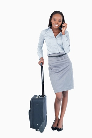 Portrait of a businesswoman with a suitcase making a phone call against a white background photo