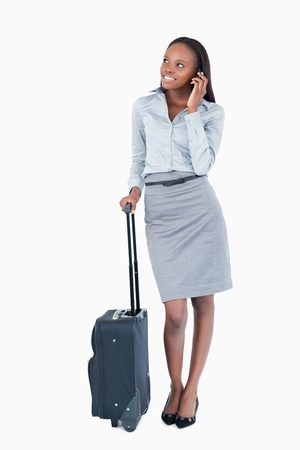 Portrait of a cute businesswoman with a suitcase making a phone call against a white background photo